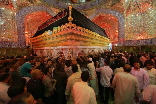 Shiite worshippers visit the shrine of Imam Ali, the son-in-law and cousin of the Prophet Muhammad and the first Imam of the Shiites, during the anniversary of his death, in the Shiite holy city of Najaf, 100 miles (160 kilometers) south of Baghdad, Iraq, early Friday, July 10, 2015. (Photo by Hadi Mizban/AP Photo)
