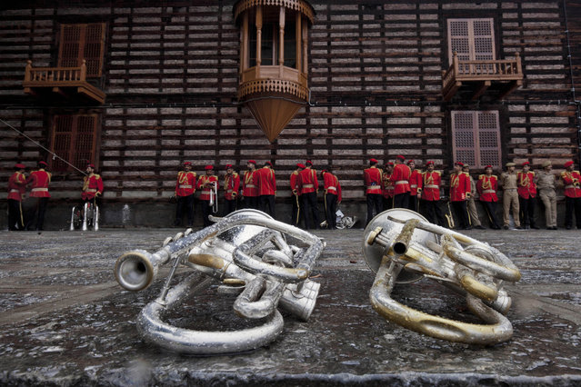 Members of Jammu and Kashmir police band, in red uniform, and policemen take cover from the rain at a shrine as trumpets are placed on the ground in Srinagar, Indian controlled Kashmir, Monday, July 13, 2015. (Photo by Dar Yasin/AP Photo)