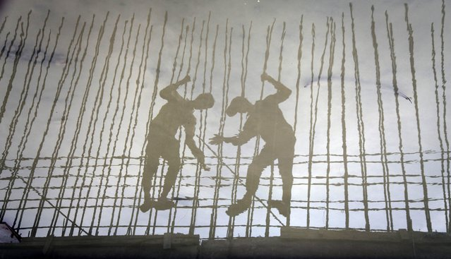 A picture rotated 180 degree shows the reflection in water as Indian labourers work at a drainage system in Mumbai, India, 07 May 2014. According to Organisation for Economic Cooperation and Development's (OECD) latest economic outlook report, India's economic growth is poised to inch up 4.9 per cent in 2014 and India's GDP is expected to pick up further momentum and grow 5.9 per cent in 2015. (Photo by Divyakant Solanki/EPA)