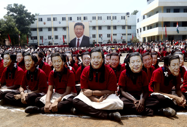 Indian school children wear face masks of Chinese President Xi Jinping to welcome him on the eve of his visit in Chennai, India, Thursday, October 10, 2019. Chinese President Xi Jinping is coming to India to meet with Prime Minister Narendra Modi on Friday, just weeks after Beijing supported India's rival Pakistan in raising the issue of New Delhi's recent actions in disputed Kashmir at the U.N. General Assembly meeting. (Photo by R. Parthibhan/AP Photo)