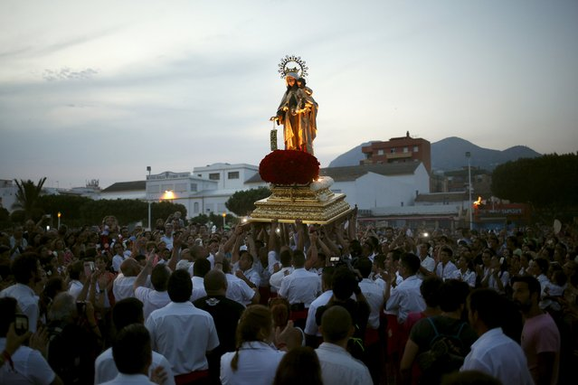 Men in traditional costumes carry a statue of the El Carmen Virgin, on its way to be carried into the sea, during a procession in Malaga July 16, 2015. (Photo by Jon Nazca/Reuters)