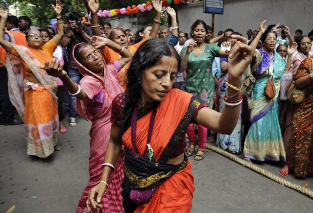 Hindu devotees dance during the Rath Yatra annual festival in Kolkata, India, Saturday, July 18, 2015. The idols of Hindu god Jagannath, his brother Balabhadra and sister Subhadra are taken out in a grand procession in a specially made chariot pulled by thousands of devotees during this festival. (Photo by Bikas Das/AP Photo)