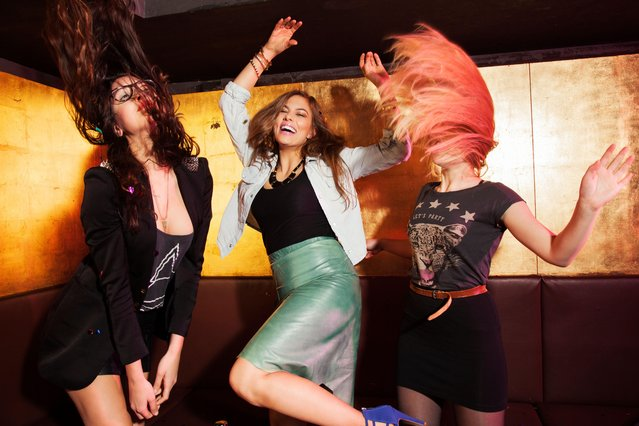 Three female friends dancing in nightclub. (Photo by Cultura Creative (RF)/Alamy Stock Photo )