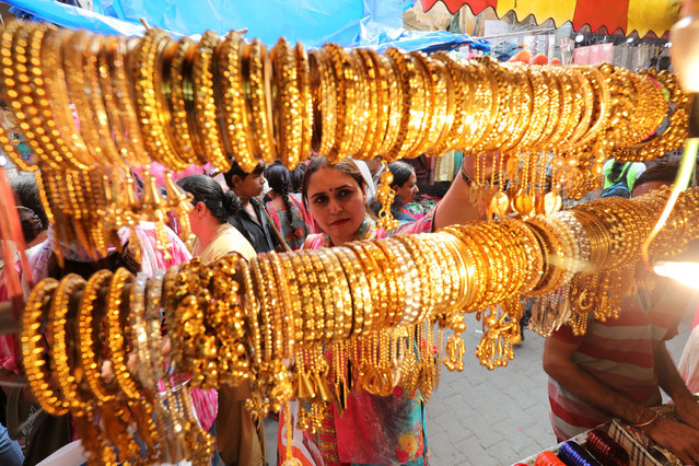 Indian women buy bangles on the eve of the Karva Chauth festival in Jammu, the winter capital of Kashmir, India, 16 October 2019. On Karva Chauth day Hindu married women observe fast and pray for the longevity and well being of their husbands. Karva Chauth festival will be observed on 17 October this year. (Photo by Jaipal Singh/EPA/EFE)