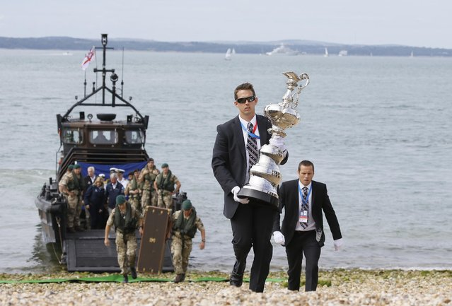 The America's Cup Trophy is carried from a Royal Marine landing craft after it arrived at the waterfront festival area in Portsmouth, England, Thursday, July 23, 2015. The event in Portsmouth is one of the America's Cup World Series qualifying events, ahead of the 35th Americas Cup in 2017. Racing takes place on July 25 and 26. (Photo by Kirsty Wigglesworth/AP Photo)