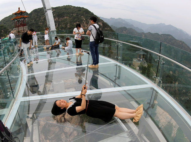 A woman takes a selfie on the glass sightseeing platform on Shilin Gorge in Beijing, China, May 27, 2016. (Photo by Kim Kyung-Hoon/Reuters)