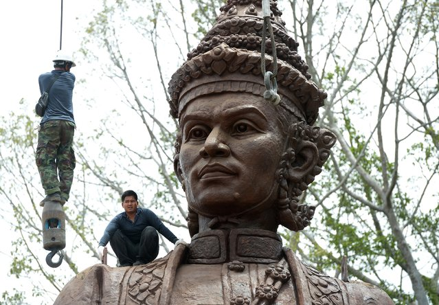 A Thai worker (L) hangs onto a hoisting cable as he and others prepare a statue of King Narai of Ayutthaya for transport from a casting factory in Lopburi province on July 24, 2015. The statue will be part of an installation at a park called Ratchapakdi in Hua Hin to honour past Thai monarchs. (Photo by Pornchai Kittiwongsakul/AFP Photo)