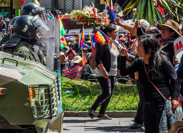 People confront riot police during the funeral procession of eight supporters of Bolivia's ex-President Evo Morales, killed when security forces lifted a siege on a fuel plant, in La Paz on November 21, 2019. Bolivia's interim President Jeanine Anez asked Congress Wednesday to approve a law that would allow for new elections, after deadly unrest following the resignation of Evo Morales and the disputed October 20 ballot. (Photo by Aizar Raldes/AFP Photo)