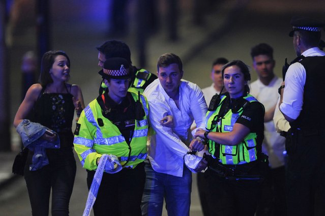 Police escort a member of public as they clear the scene of a terror attack on London Bridge in central London on June 3, 2017. (Photo by Daniel Sorabji/AFP Photo)