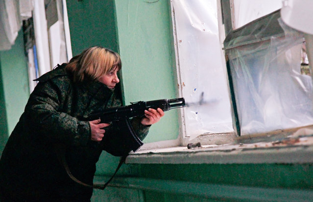 An armed pro-Russian militant holds her position inside of a damaged school in Zaytseve village of Donetsk area, Ukraine, 14 March 2016. Pro-Russian rebels attacked Ukrainian army positions at least 44 times in the past 24 hours, including 38 times in the Donetsk sector, five times in the Mariupol sector and once in the Luhansk sector, the press center of the Anti-Terrorist Operation (ATO) reported. (Photo by Alexander Ermochenko/EPA)
