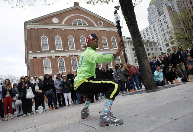 In this Friday, May 6, 2016 photo, Scoogie performs with Breeze Team at Faneuil Hall, rear, in Boston. Officials are considering regulations on street performers citywide because they say breakdance crews and bucket drummers performing in front of Faneuil Hall, one of Boston's most visited tourist sites, are using inappropriate language, playing music too loud, aggressively soliciting donations and bullying other performers out of the high traffic area. (Photo by Michael Dwyer/AP Photo)