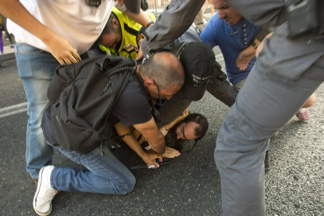 A police officer removes a knife from ultra-Orthodox Jew Yishai Schlissel after he stabbed people during a gay pride parade in Jerusalem on Thursday, July 30, 2015. (Photo by Sebastian Scheiner/AP Photo)
