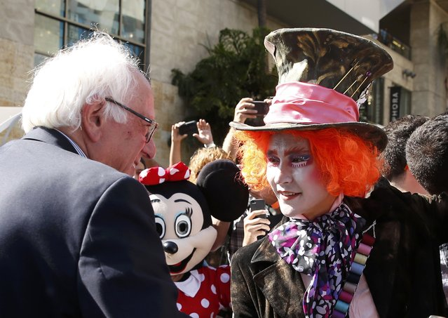 Democratic U.S. presidential candidate Bernie Sanders greets a supporter dressed as the Mad Hatter on Hollywood Boulevard in Hollywood, Los Angeles, California, U.S., June 7, 2016. (Photo by Lucy Nicholson/Reuters)