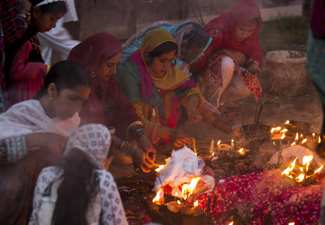 Pakistani Muslim devotees visit and light oil clay lamps at a local shrine in suburbs of Islamabad, Pakistan, Thursday, July 23, 2015. People usually visit shrines on Thursday and Friday, to get their wishes fulfilled. (Photo by B. K. Bangash/AP Photo)