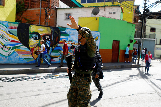 A Venezuelan national guard shouts to locals as they patrol a neighborhood after a protest over food shortage and against Venezuela's government in Caracas, Venezuela, June 10, 2016. (Photo by Ivan Alvarado/Reuters)