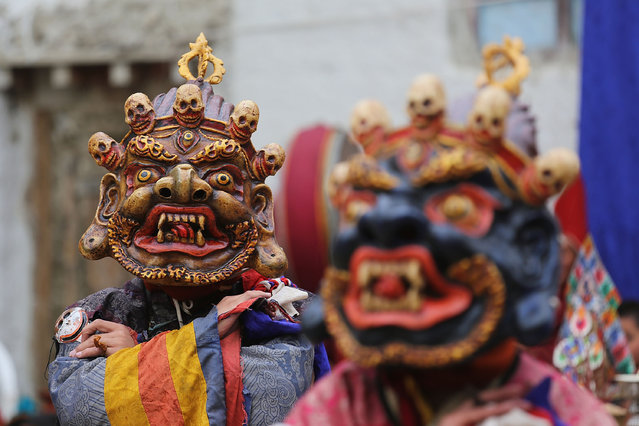 Elaborately dressed monks costumed as wrathful guardian spirits perform ceremonial dances during the Tenchi Festival on May 25, 2014 in Lo Manthang, Nepal. The Tenchi Festival takes place annually in Lo Manthang, the capital of Upper Mustang and the former Tibetan Kingdom of Lo. Each spring, monks perform ceremonies, rites, and dances during the Tenchi Festival to dispel evils and demons from the former kingdom. (Photo by Taylor Weidman/Getty Images)