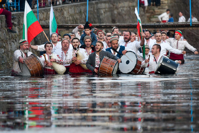 """Bulgarian men perform the traditional """"Horo"""" dance in the icy winter waters of the Tundzha river in the town of Kalofer, as part of Epiphany Day celebrations on January 6, 2020. As a tradition, an Eastern Orthodox priest throws a cross in the river and it is believed that the one who retreives it will be healthy throughout the year as well as all those who dance in the icy waters. (Photo by Nikolay Doychinov/AFP Photo)"""