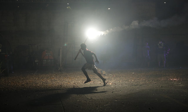 A Filipino boy runs with a bright firework as they celebrate the coming of the New Year early Wednesday, January 1, 2020 in Manila, Philippines. Filipinos welcome the New Year with noise and firecrackers in the belief that this will drive away bad spirits and bring in good luck. (Photo by Aaron Favila/AP Photo)