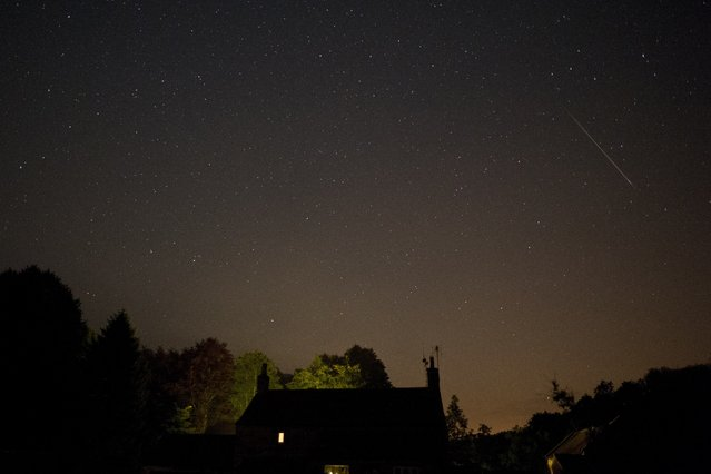 A meteor passes across the sky during the peak in activity of the annual Perseids meteor shower in the village of Rievaulx, near Helmsley, northern England on August 13, 2015. (Photo by Oli Scarff/AFP Photo)