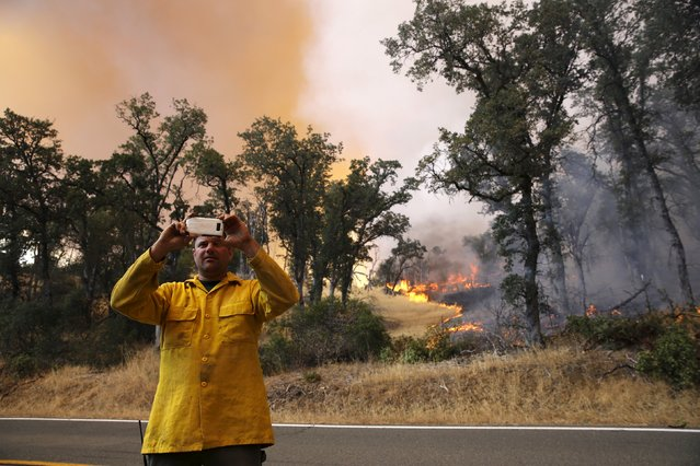 A firefighter snaps a photograph as the so-called Jerusalem Fire burns behind him in Lake County, California, August 12, 2015. (Photo by Robert Galbraith/Reuters)