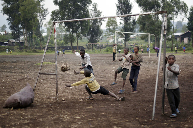 Congolese children play football on a dirt field in Goma, Democratic Republic of Congo, Saturday June 18, 2016. One goal was scored with the old deflated ball the children use to play with. (Photo by Jerome Delay/AP Photo)