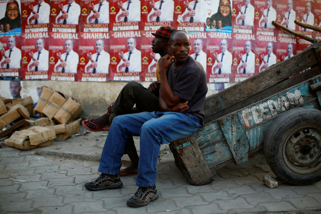 Men sit on the side of a cart next to a wall pasted with campaign posters ahead of the presidential election in Mombasa, Kenya August 7, 2017. (Photo by Siegfried Modola/Reuters)