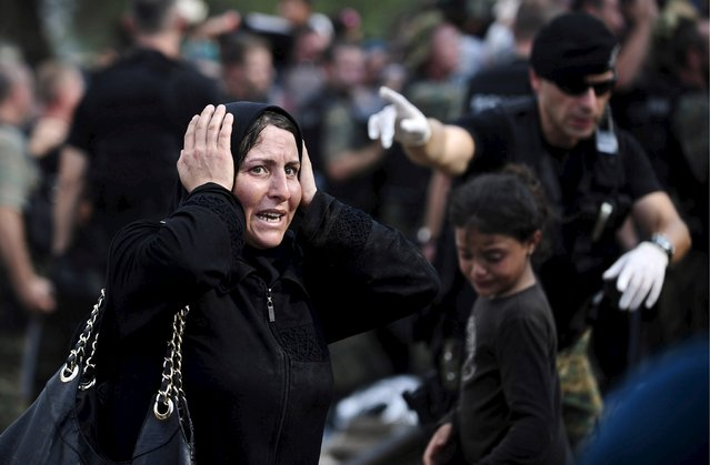 A woman reacts to the police at the border line dividing Macedonia and Greece August 21, 2015. (Photo by Ognen Teofilovski/Reuters)