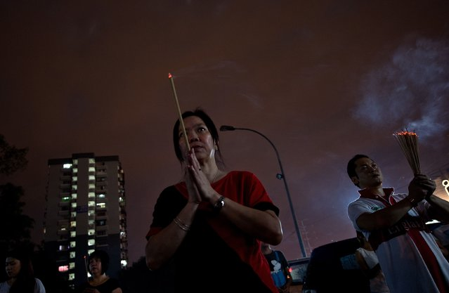 """Ethnic Chinese devotees burn incense sticks and pray before setting a fire to a statue of Chinese deity """"Da Shi Ye"""" or Guardian God of Ghosts during the Hungry Ghost festival in Kuala Lumpur, late on August 10, 2014. (Photo by Manan Vatsyayana/AFP Photo)"""