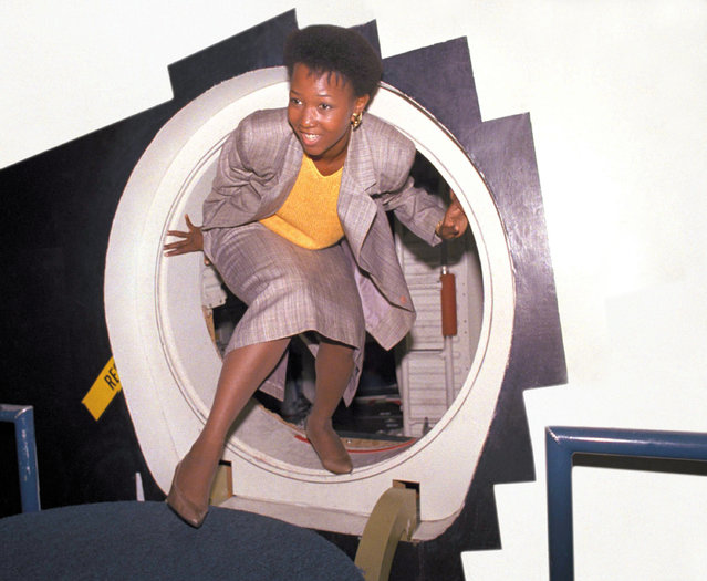 Dr. Mae C. Jemison, the first black female astronaut candidate, steps through the hatch of a space shuttle trainer at the Johnson Space Center in Houston, Texas, August 25, 1987. Jemison was one of 15 candidates that met the press on Monday. The candidate class, first since the Challenger disaster, will start training this week to become astronauts. (Photo by Ed Kolenovsky/AP Photo)