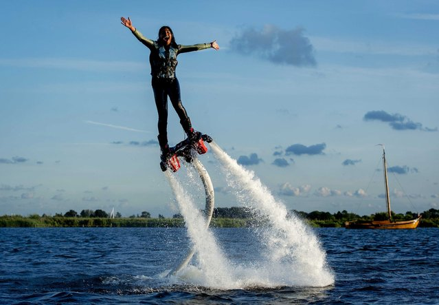 A picture made available on 14 August 2014 shows a girl using a flyboard, a water jet pack which connects to a personal water craft with a hose at the Kaag Lakes, in Kaag, the Netherlands, 13 August 2014. A flyboard rider stands on a board connected by a long hose to a watercraft. Water is forced under pressure to a pair of boots which provide thrust for the rider to fly up in the air.  (Photo by Robin van Lonkhuijsen/EPA)