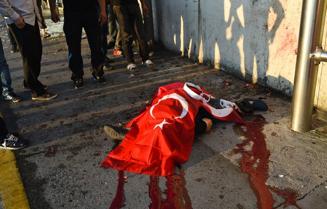 A civilian killed by Turkish soldiers lies on a ground on the Bosphorus bridge in Istanbul on July 16, 2016. (Photo by Bulent Kilic/AFP Photo)