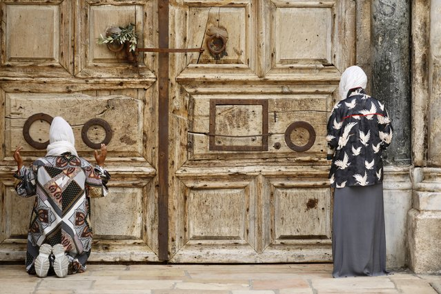 Women pray iin front of the closed Church of the Holy Sepulchre, a place where Christians believe Jesus Christ was buried, as a palm hangs on the door, in Jerusalem's Old City, Sunday, April 5, 2020. The traditional Palm Sunday procession was cancelled due to restrictions imposed to contain the spread of the coronavirus. (Photo by Ariel Schalit/AP Photo)