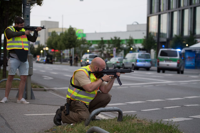 Police officers point their weapons outside the Olympia mall in Munich, southern Germany, Friday, July 22, 2016 after several people have been killed in a shooting. (Photo by Sebastian Widmann/AP Photo)