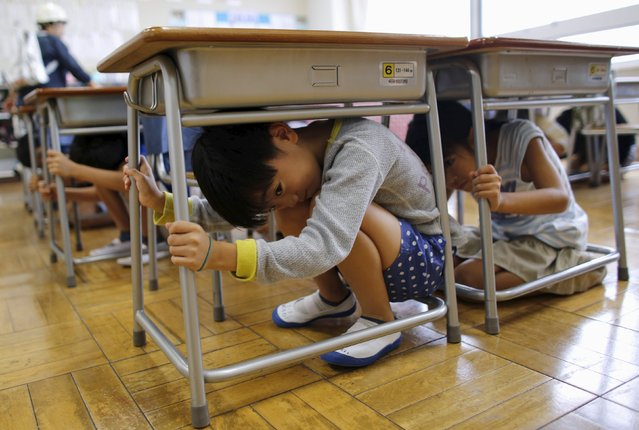School children take shelter under desks during an earthquake simulation exercise at an elementary school in Tokyo September 1, 2015. The annual exercise is held nationwide on the anniversary of the 1923 Great Kanto Earthquake to practise the response to major natural disasters. (Photo by Toru Hanai/Reuters)