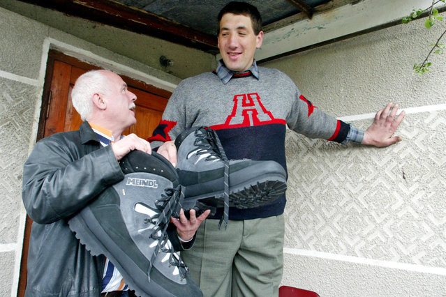 German shoemaker Georg Wessels (L) presents a pair of shoes to Ukraine's Leonid Stadnyk, who stands at a height of 2.53 metres (eight feet four inches) and may be considered the world's tallest living man, near his house in the village of Podolyantsi in Ukraine's Zhytomyr region, about 200 km (124 miles) from the capital Kiev, May 6, 2005. Georg and his brother (Peter) Wessels, owners of a company manufacturing made-to-measure orthopaedic footwear, brought Stadnyk a pair of size 64 shoes. (Photo by Reuters/STR New)