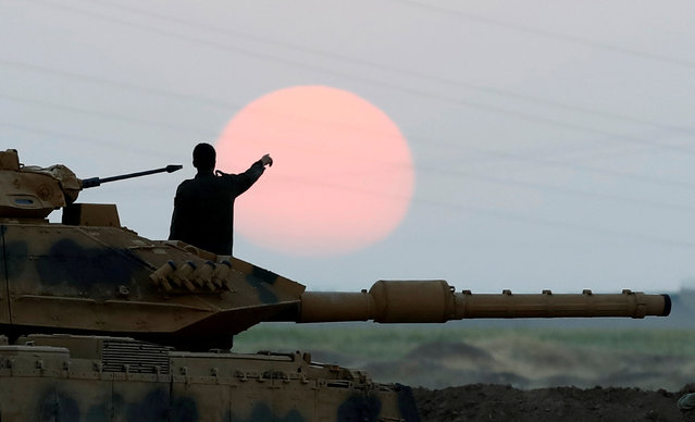 A Turkish soldier points as he stands on a tank during a military exercise near the Turkish-Iraqi border in Silopi, Turkey, September 22, 2017. (Photo by Umit Bektas/Reuters)