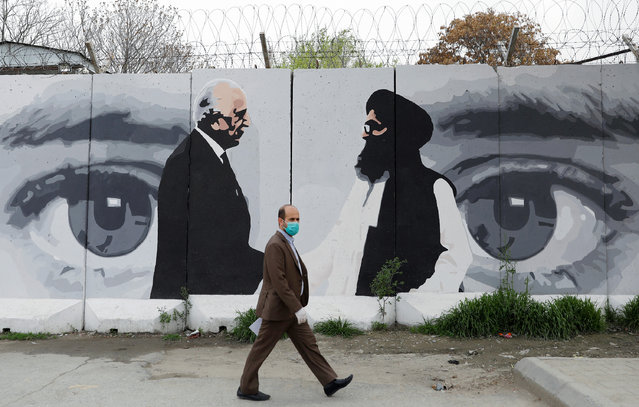 An Afghan man wearing a protective face mask walks past a wall painted with photo of Zalmay Khalilzad, U.S. envoy for peace in Afghanistan, and Mullah Abdul Ghani Baradar, the leader of the Taliban delegation, in Kabul, Afghanistan on April 13, 2020. (Photo by Mohammad Ismail/Reuters)