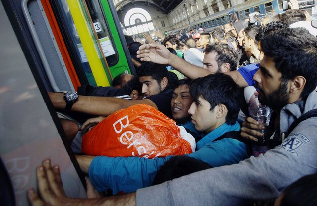 Migrants of several countries enter a local train with direction to the Hungarian-Austrian border at Keleti (East) railway station in Budapest on September 3, 2015. A train carrying between 200 and 300 migrants left Budapest's main international train station and headed toward the Austrian border, after authorities re-opened the station to migrants. (Photo by Peter Kohalmi/AFP Photo)