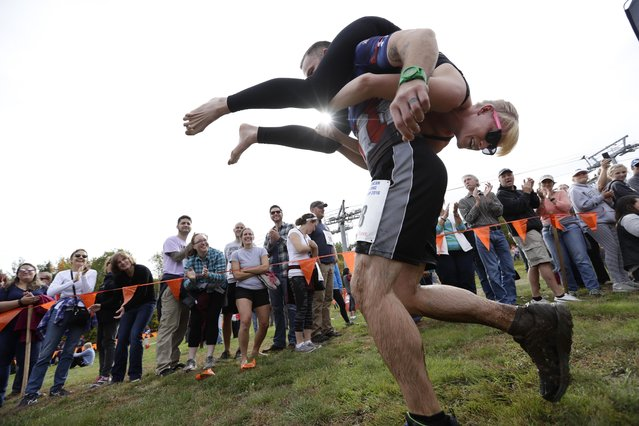 In this October 8, 2016 file photo, Jaime Devine is carried by her husband, Thomas Devine, of Boston, Mass., during the North American Wife Carrying Championship at the Sunday River Ski Resort in Newry, Maine.  Dozens of participants are vying for cash and beer  in the North American Wife Carrying Championship. More than 60 couples are registered, and more are on a waiting list, for the annual event Saturday, Oct. 7, 2017 at the Sunday River in Maine. (Photo by Robert F. Bukaty/AP Photo)