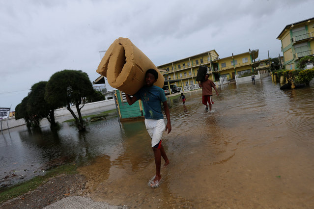 A man (L) carries a mattress as he leaves a school used as a shelter, after Hurricane Earl hit, in Belize City, Belize August 4, 2016. (Photo by Henry Romero/Reuters)