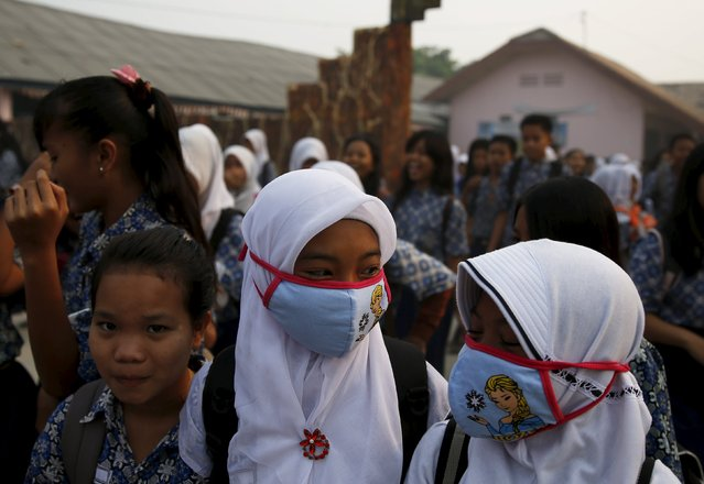 Students, wearing face masks, walk in front of their school as they prepare to head home due to the unhealthy quality of air in Palembang, on Indonesia's Sumatra island, September 10, 2015. (Photo by Reuters/Beawiharta)