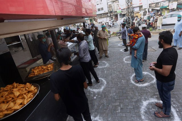 People maintaining a level of social distancing wait their turn to get traditional food from a bakery to break their fast on the first day of Ramadan, in Lahore, Pakistan. Saturday, April 25, 2020. Millions of Muslims have started Ramadan, the holiest month on the Islamic calendar, under the coronavirus lockdown or strict social restrictions. (Photo by K.M. Chaudary/AP Photo)