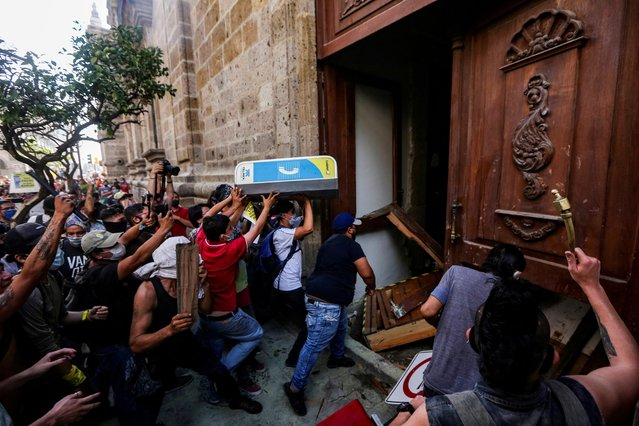 Demonstrators smash down a door of the Jalisco State Government Palace during a protest to demand justice for Giovanni Lopez, a construction worker who died after being arrested for not wearing a face mask in public, during the coronavirus disease (COVID-19) outbreak in Guadalajara, Mexico on June 4, 2020. (Photo by Fernando Carranza/Reuters)
