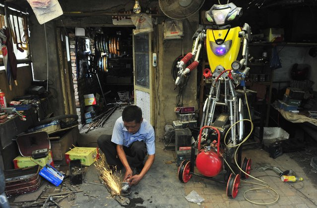 A 49-year-old electric bike mechanic who identified himself only as Wu welds a component to fit onto his newly-made robot (R) at his repair shop in Shenyang, Liaoning province June 25, 2012. Wu spent over 10 days to make this nearly two-meter high robot using parts from abandoned electric bikes. The robot, which is able to walk and pump up tires by itself, is still under modification, according to local media. (Photo by Reuters/Stringer)