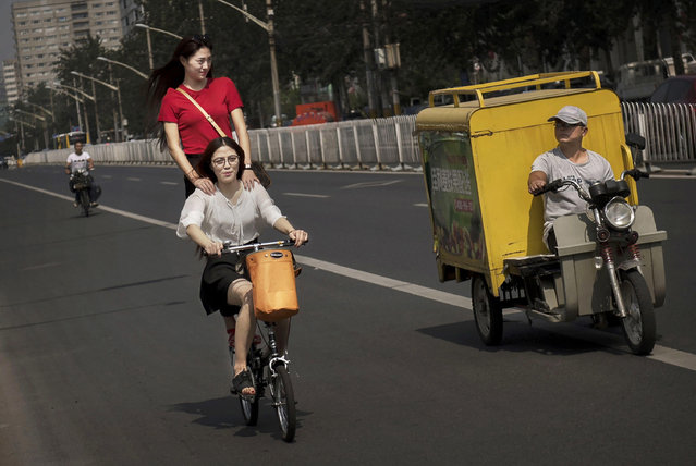Chinese women ride a bicycle together on a street September 10, 2014 in Beijing, China. (Photo by Kevin Frayer/Getty Images)