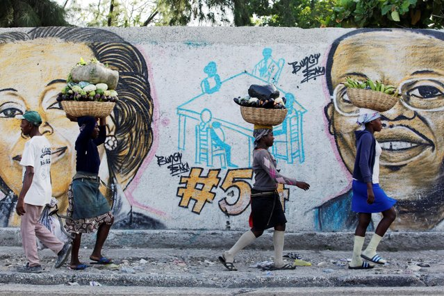 Residents walk next to a graffiti of presidential candidate Maryse Narcisse together with ousted deposed president Jean Bertrand Aristide in a street of Port-au-Prince, Haiti, July 22, 2016. (Photo by Andres Martinez Casares/Reuters)