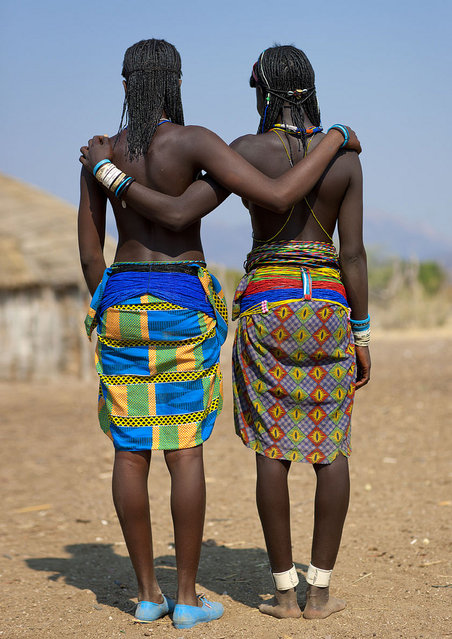 """Show us our butts! Mucawana tribe – Angola. In Soba village, the Muhacaona (Mucawana) tribe, perhaps the best place i have visited. They use cow dung and fat to make this so nice haircut, and love the beads. They asked me to make pictures of their backs... and butts to see on the camera screen if everything was perfect!"". (Eric Lafforgue)"