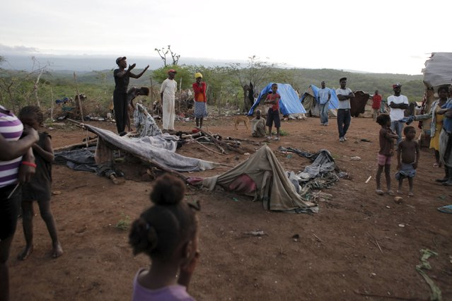 Residents stand around an uninhabited makeshift tent that was torn down at a refugee camp for Haitians returning from the Dominican Republic on the outskirts of Anse-a-Pitres, Haiti, September 7, 2015. (Photo by Andres Martinez Casares/Reuters)