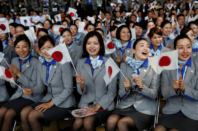 Flight attendants wave Japan's national flags while they wait for the arrival of the Olympic flag during a ceremony to mark the arrival of the flag at Haneda airport  in Tokyo, Japan, August 24, 2016. (Photo by Kim Kyung-Hoon/Reuters)