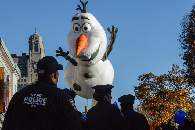 """The Olaf from """"Frozen"""" balloon is led down Central Park West as NYPD officers look on during the annual Macy's Thanksgiving Day parade on November 23, 2017 in New York City. The Macy's Thanksgiving Day parade is the largest parade in the world and has been held since 1924. (Photo by Stephanie Keith/Getty Images)"""